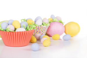 Easter Candy in colorful cupcake wrappers with green grass confetti and dyed Easter egg